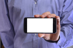 Young man in a blue shirt is holding a phone with the white scre Royalty Free Stock Images