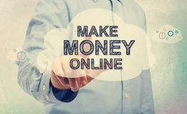 Young man in blue shirt pointing at Make Money Online. Text royalty free stock photo