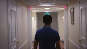 Young man in blue shirt walking along corridor at hallway hotel back view. Man walking on light corridor in cozy hotel interior stock video footage