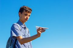 A young man on a blue sky holding a paper plane, the concept of flight and travel royalty free stock images