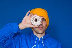 Man in a blue sport 90s style jacket and yellow hat holding sweet donut  on his eyes over blue background. Young man in a blue sport 90s style jacket and yellow stock image