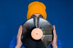 Man in a blue sport 90s style jacket and yellow hat holding vinyl record, man hides his face under vinyl disc. Young man in a blue sport 90s style jacket and royalty free stock image