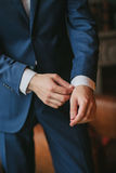 A young man in a blue suit adjusts his shirt cufflinks. Hands close-up on a brown chair background royalty free stock photography