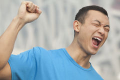 Young man in blue T-shirt with fist raised in the air, Beijing Royalty Free Stock Photography