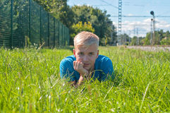 Young man in blue t-shirt lying on the green grass Stock Photography