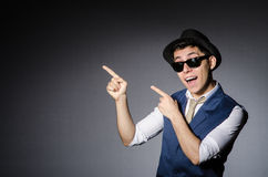 Young man in blue vest and hat against gray Stock Photos