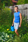 A young man with a blue watering can around the garden with cabb Stock Photos