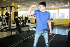 A young man in a blue. T-shirt. gym. demonstrates the biceps Stock Photos