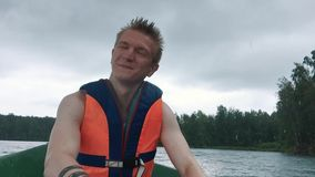 A young man in a boat rowing wooden oars on the water. Life jacket on the body of a man. stock footage