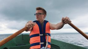 A young man in a boat rowing wooden oars on the water. Life jacket on the body of a man. stock video footage
