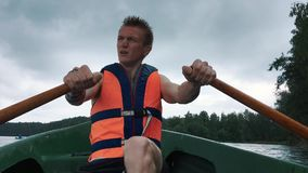 A young man in a boat rowing wooden oars on the water. Life jacket on the body of a man. stock video