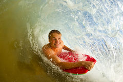 Young man body boarding. Youthful young man Boogie Boarding Blue Wave stock photos