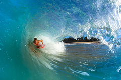 Young man body boarding. Youthful young man Boogie Boarding Blue Wave Royalty Free Stock Images
