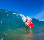 Young man body boarding. Youthful young man Boogie Boarding Blue Wave stock photo