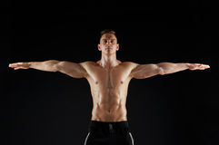 Young man or bodybuilder with bare torso. Sport, bodybuilding, fitness and people concept - young man or bodybuilder with bare torso over black background Royalty Free Stock Images