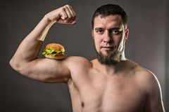 Young man bodybuilder holding burger, unhealthy eating habits. Athletic man with fast food on a gray background Stock Image