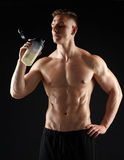 Young man or bodybuilder with protein shake bottle. Sport, bodybuilding, fitness and people concept - young man or bodybuilder with protein shake bottle and bare royalty free stock image