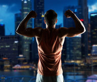 Young man or bodybuilder showing biceps. Sport, fitness, bodybuilding, strength and people concept - young man or bodybuilder showing biceps over night city Royalty Free Stock Photos