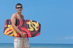 Young man with boogie board. Attractive young man with boogie board at the beach stock images