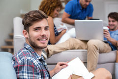 Young man with book while friends in background Stock Photography
