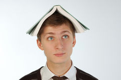 Young man with a book on his head Royalty Free Stock Photo