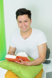 Young man with a book at home stock photos