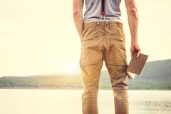 Young Man with book outdoor with scandinavian lake on background Stock Photos