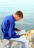 Young Man with a Book outdoor. Young Man with a Book sit on the Stone at the Seaside Royalty Free Stock Photography