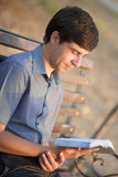 Young man with a book in the park Royalty Free Stock Photos