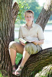 The young man with the book in park on  lake Royalty Free Stock Photos