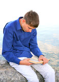 Young Man with a Book. Sit on the Stone at the Seaside Royalty Free Stock Photo