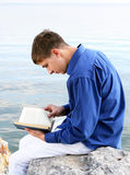Young Man with a Book. Sit on the Stone at the Seaside Stock Photo