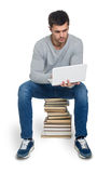 Young man with books and computer Royalty Free Stock Images