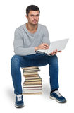 Young man with books and computer Stock Image