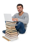 Young man with books and computer Stock Images