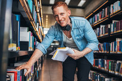 Young man at bookshelf at public library Royalty Free Stock Photo