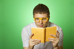 Young man bookworm reading. Young attractive man in a shirt and yellow glasses, bow tie on a green background reads the yellow book. Bookworm stock photography