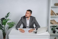 A young man is bored in the workplace. The teacher prepares for the lecture. A businessman in gray suit works at the computer Stock Photos