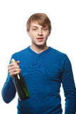 Young man with a bottle of champagne in a blue sweater.  Royalty Free Stock Photography