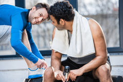 Young man with bottle of water sitting on tyre and talking to friend. Handsome young men with bottle of water sitting on tyre and talking to friend stock image