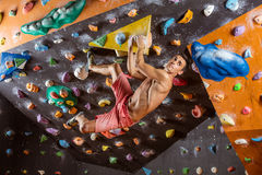 Young man bouldering in indoor climbing gym Stock Images