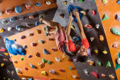 Young man bouldering in indoor climbing gym Stock Photo