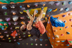Young man bouldering in indoor climbing gym Royalty Free Stock Photo