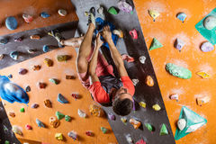 Young man bouldering in indoor climbing gym Royalty Free Stock Photos