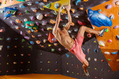 Young man bouldering in indoor climbing gym Stock Photography