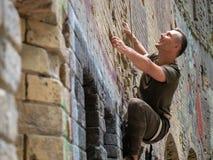 Young man bouldering outdoor climbing. stock photography