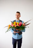 Young man with bouquet of flowers in his hands. Royalty Free Stock Image