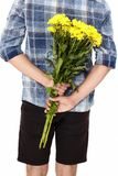 Young man with a bouquet of yellow flowers behind his back. Isolated on white background. Mother day. Valentine. Summer concept stock photo