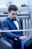 Young man in boutique of clothing. Stock Image