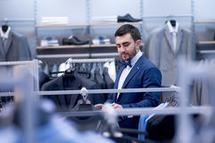 Young man in boutique of clothing. Royalty Free Stock Photo